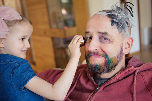 Girl (4-5) having fun putting makeup on her bemused father