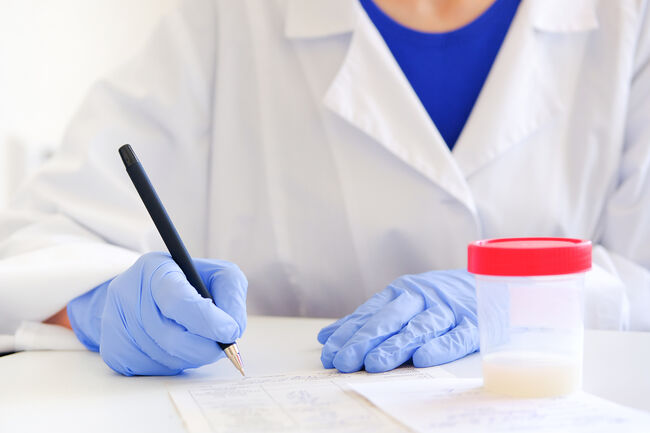 The doctor in medical gloves with a pen in his hands writes the results of studies or fills out forms documents. Next to the container with the semen analysis. Donor sperm for artificial insemination.