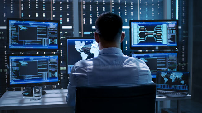 System Security Specialist Working at System Control Center. Room is Full of Screens Displaying Various Information.