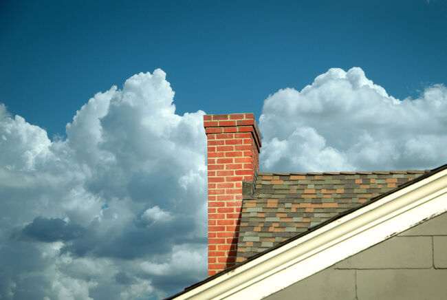 Part of tiled roof with brick chimney against clouds