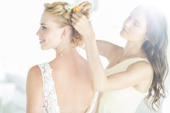 Bridesmaid helping bride with hairstyle in garden