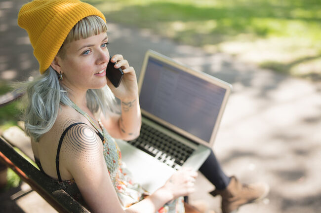 Young woman sat using her laptop and talking on the phone in the park