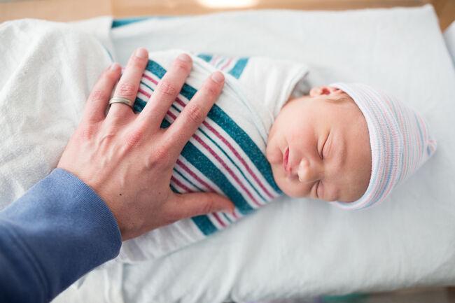 Father Rests Hand on Sleeping Newborn