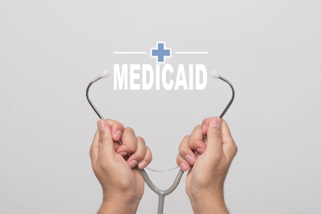 """Hands holding a stethoscope and word """"MEDICAID""""  medical concept."""