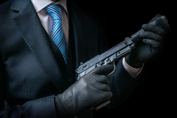 Mafia man holds pistol with silencer in hands. Low key.
