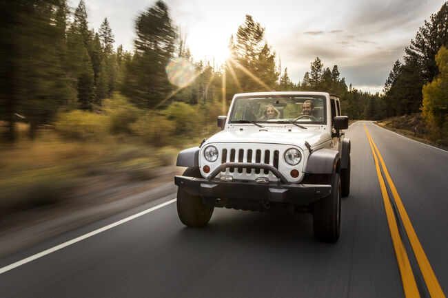 Young couple driving jeep on road trip, Lake Tahoe, Nevada, USA