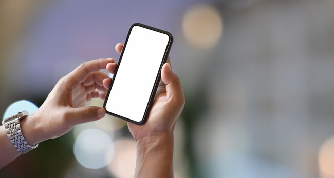 Man hands holding blank screen smartphone with blurred light bokeh background