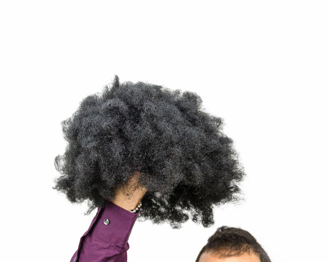 man holding a wig in hand