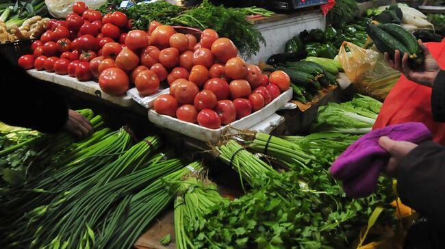 A vegetable vendor counts money as peopl