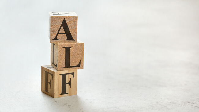 Pile with three wooden cubes - letters ALF for Always Listen First on them, space for more text / images on right side.