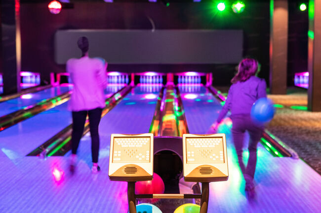 Computer monitors against teenage girls throwing balls on parquet floor at bowling alley