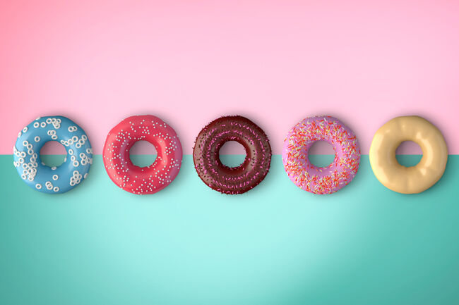 Close-Up Of Donuts Over Colored Background
