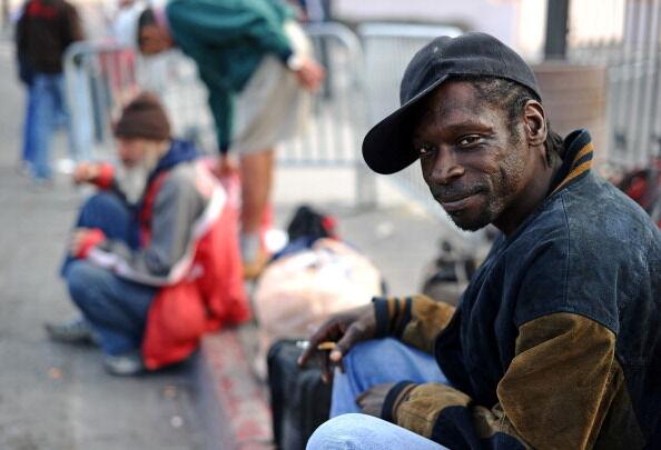 A homeless man waits to get food donatio