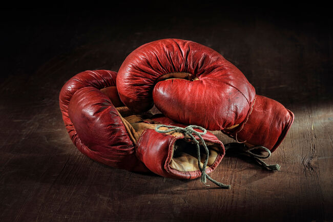 Close-Up Of Red Boxing Gloves Over Wooden Background