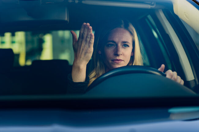 Young frustrated woman driving car