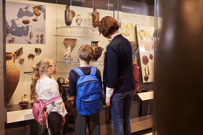 Teacher And Pupils Looking At Artifacts On Display In Museum