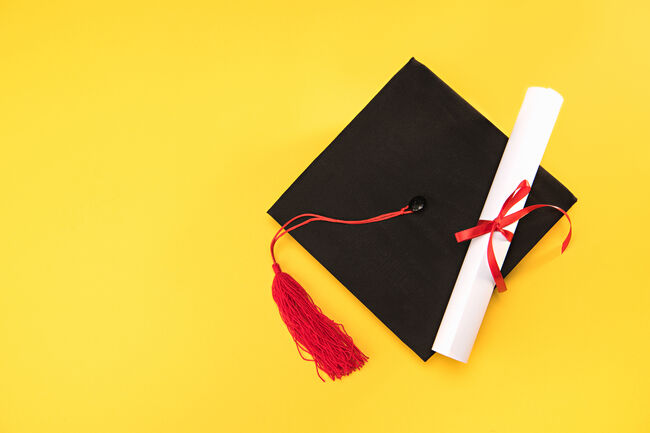 Top view of graduation mortarboard and diploma on yellow background, education concept