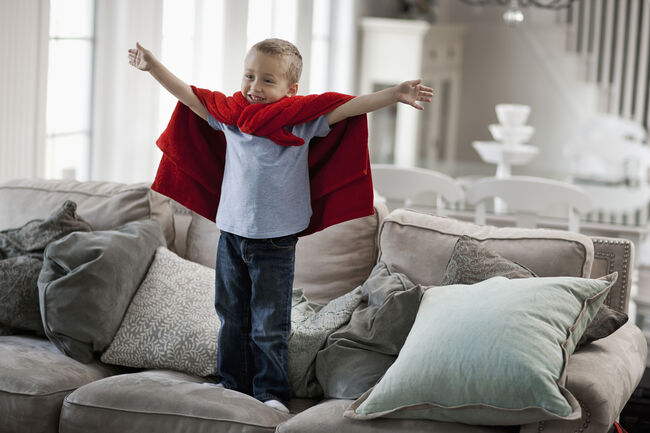 A child standing wearing a red cape, arms raised in a superhero pose.