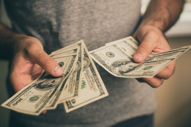 A man holds dollars in his hands