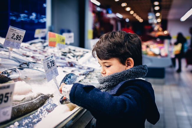 Boy touching a fish in the fish market