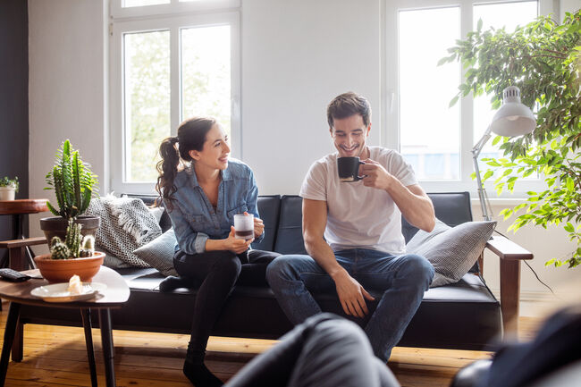 Couple having coffee together in living room
