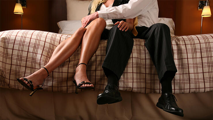 Passionate Lovers Sitting on Edge of Bed Touching Legs Hugging