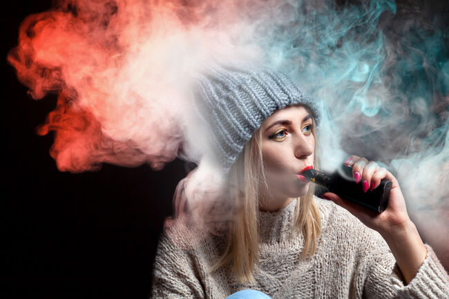 Blonde girl in a knitted sweater and hat holds an electronic cigarette vape in her hand with a manicure and exhales a lot of colored red and green smoke, with red lipstick on a black background.