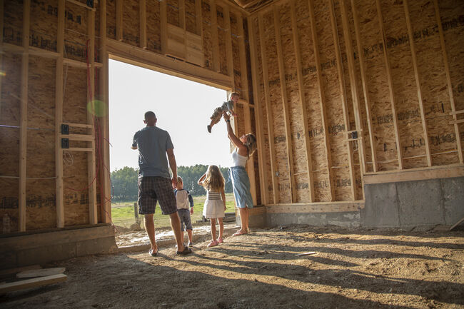 Young family standing in rural barn under construction