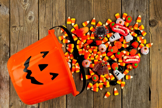 Halloween Jack o Lantern pail with spilling candy over wood (Getty Images)