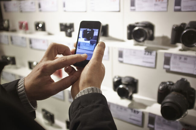 Mid adult man photographing camera's in shop display using smartphone