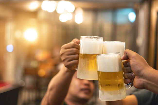 Beer glasses raised in a toast. Close-up hands with glasses. Blurred bar interior at the background