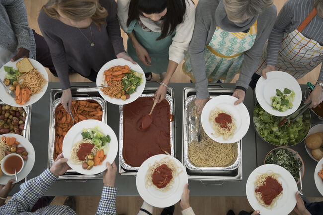 Overhead view people serving food at soup kitchen community dinner