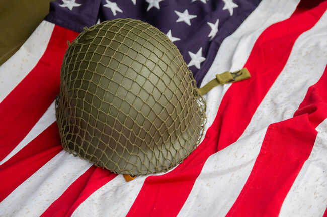 Soldier's helmet and the times of the Second World War and the US flag. Patriotism