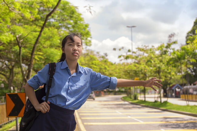 young asian teenage female hailing taxi cab at road side in sunny day. malaysian student girl waiting for car pool in kuala lumpur after school