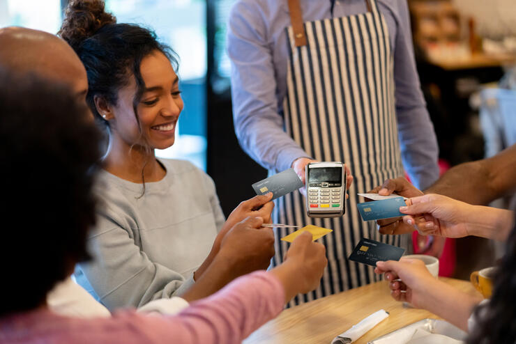 Group of friends paying with a credit card at a restaurant and splitting the bill