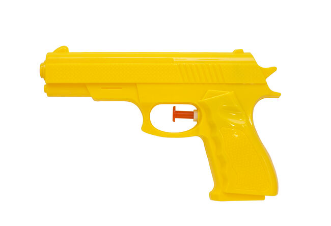 Close-Up Of Yellow Squirt Gun Against White Background