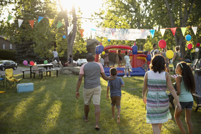 Family arriving at summer neighborhood block party in park