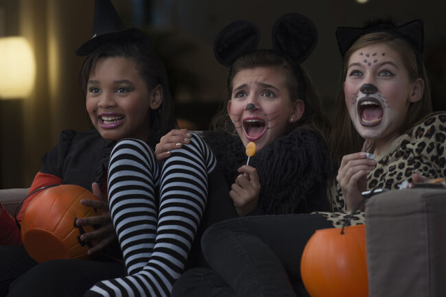 Girls in costumes watching scary movie together on Halloween