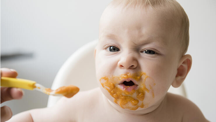 Mother feeding messy baby son with spoon in high chair