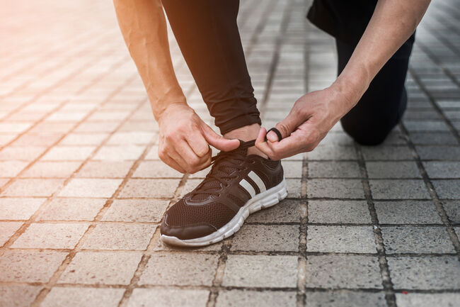 Low Section Of Man Tying Shoelace While Kneeling On Footpath