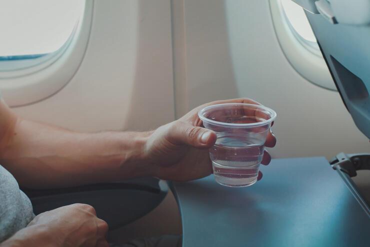 Passenger drinking water in airplane during flight.
