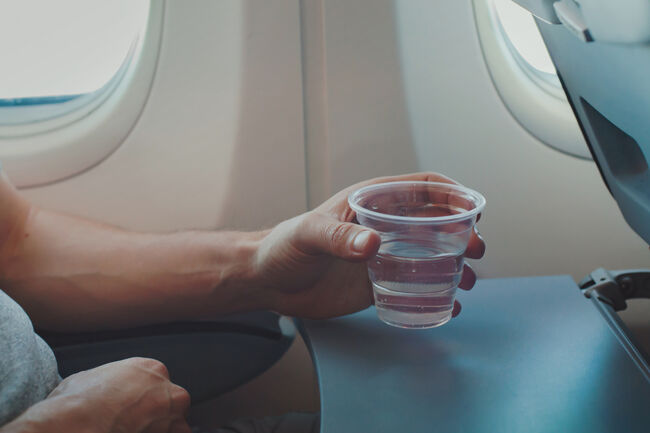 Passenger drinking water in airplane during flight.