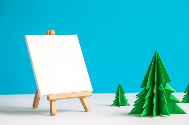 Easel and blank art canvas with origami christmas trees winter landscape abstract.