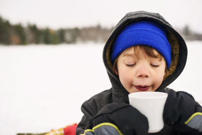 Boy standing in the snow drinking hot chocolate