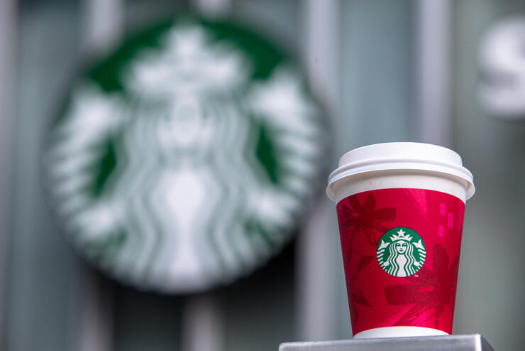 A paper coffee cup and Starbucks logo.   Starbucks will