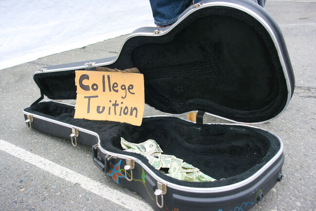 """Guitar case open with money for tips with """"College Tuition"""" sign"""