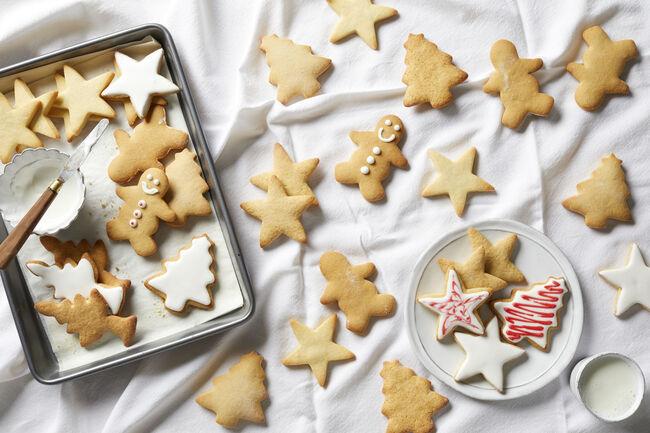 Christmas sugar cookies being iced, overhead view