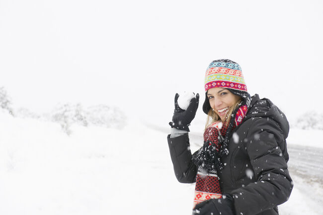 Hispanic woman throwing snowballs