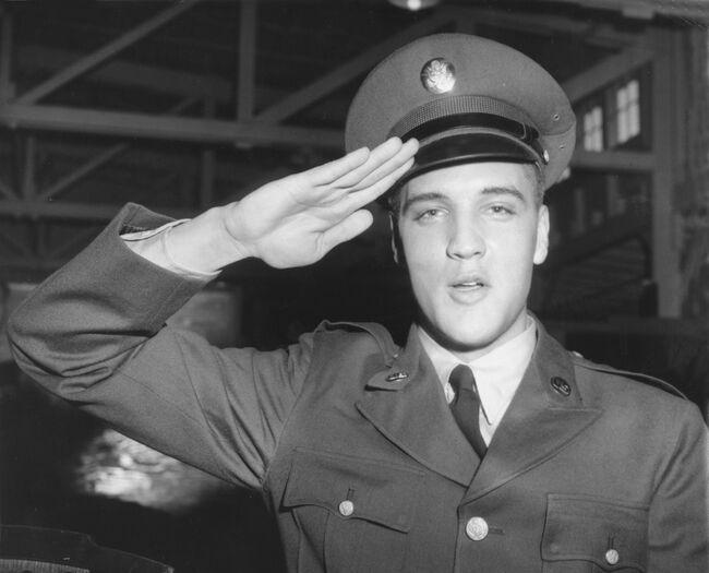 Elvis Presley salutes in his Army uniform