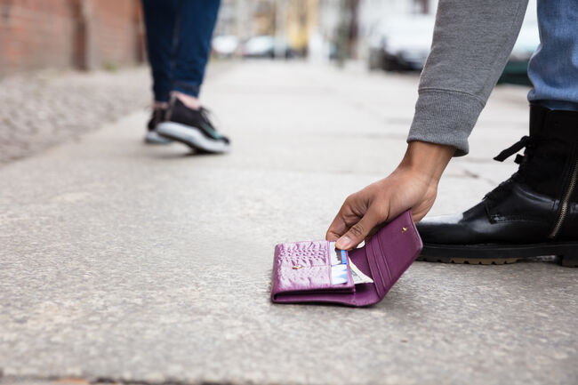 Person Picking Up Lost Purse